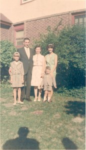 My immediate family circa 1965. That's me at about age 10 on the far left with my father's arm around me. My mother is in the center with my sister to her right and my brother in front. The carousel clothesline is to our left just out of sight.